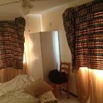 Dormitorio con mantas en las ventanas para quitar la luz.