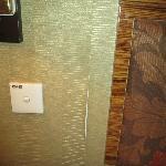 Peeling wallpaper beside the bed