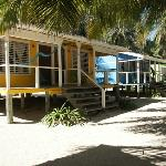 Colorful cabanas with two beds, bathroom and porch with hammock