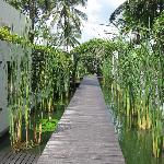 a teak walkway leading from the spa by some beach villa rooms to the main resort grounds