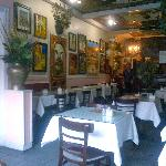 View of the restaurant with owner's colourful paintings on the walls and ceilings.