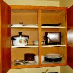 Open cupboard with dishes. Toaster.