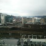 Utsikt fra 15. etasje på dagtid. Bjørvika og Oslo Operahus kan skimtes mot havet.