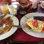 pancakes, fresh orange juice, coffee, omelette, black beans and fresh homemade bread