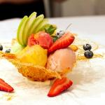Homemade sorbets and fresh seasonal fruits in a spun toffee basket