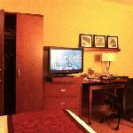 Storage, TV, & desk across from sofa in king room