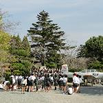 A Japanese school class posing in front of the monument