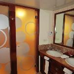 vanity area with door to walk in shower and door to toilet