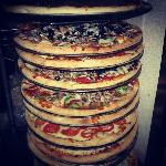 Hand tossed pizzas stacked high.