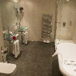 a very large stunning bathroom with roll top bathe and large shower