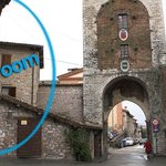 the little hotel is next to a medieval gate and tower in Gubbio.
