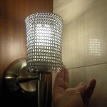 The bathroom light fixture(s) with chain mail shade.
