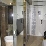 the entrance and the divided room with the glass panelled bath compartment and WC