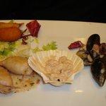 Antipasto tiepido di mare, cocktail di gamberetti, calamaro ripieno, chele di granchio e gamberi