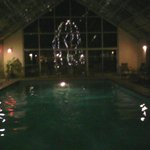Large indoor pool with lighted fir tree outside the big window.