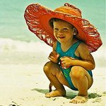 Little girl in big hat on beach
