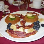 bacon, pancakes, maple syrup and fruit arranged for fun