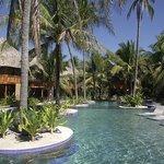 La piscina cuenta con sillas de madera para tomar el sol o descansar.