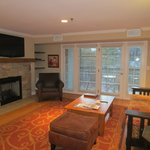 Sitting area, fireplace, wall-mounted flat-screen TV, and doors to balcony, suite 404