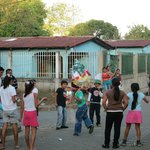 Area children knock candy out of a piñata.