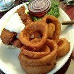 Buffalo Chicken sandwich w/ lettuce, tomato, onion, blue cheese on house made roll w/ onion ring