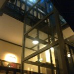 A modern glass elevator is fitted in the stairwell.