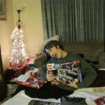 Son opening one of his gifts in the living room