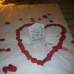 Rose Pedals on bed with Porcelain sign saying Happy Anniversary