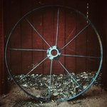 An Old Wheel to an Old Wagon on the Outside of The Round Barn