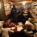 Engage with community projects such as Amani Kibera's library in Nairobi's slums