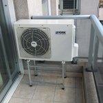 Ar condicionado novo, localizado na sacada do apartamento.