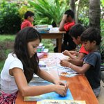Local kids playing with jigsaw-puzzles, gifts from other guests.