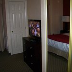TV and mirrored closed doors in bedroom