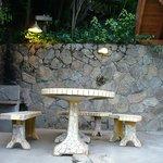 entrada de la cabaña y vista de la mesa de jardin y la parrilla