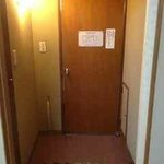 Entryway to room (genkan) where one leaves shoes. Toilet room on left, sink/shower & tub room on