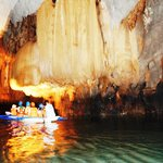 Tour boat under formations of stalactites and stalagmites inside the cave
