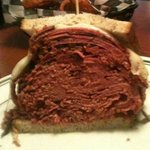 Half of the Pastrami & Corned Beef on Rye with Melted Provolone.