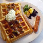 Waffles with pistachio marmalade, fruit garnish, and breakfast sausage.