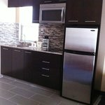 Kitchenette room with ceramic cook top, microwave and refrigerator/freezer.