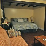 The room with king sized bed, refrigerator and couch