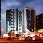 Crowne Plaza Dubai's exterior at night along Sheikh Zayed Road