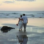 newly married couple strolling on the beach
