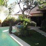 Pool, garden and entrance to villa building