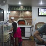 Looking at the pizza oven and the chef in action