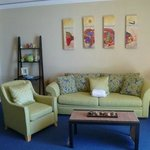 Large sitting area with pullout sleeper sofa, cute furniture, but beachy feel