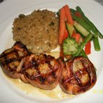 Salmon wrapped scallops with risotto cake and veggies.