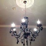 Interesting chandelier above bed