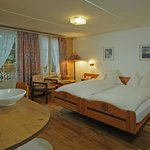 Cozy double room category Alpenglueck with private bathroom, a comfortable armchair and cable TV