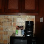 Kitchenette with sink, coffee, fridge, microwave and dishware.