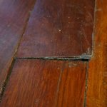 Warped floor board in front of door